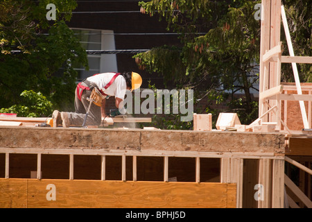 Carpenter Sawing with circular saw on second floor - Stock Photo
