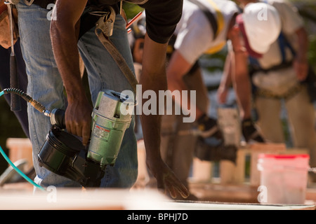 Carpenters working with nail guns at a construction site - Stock Photo