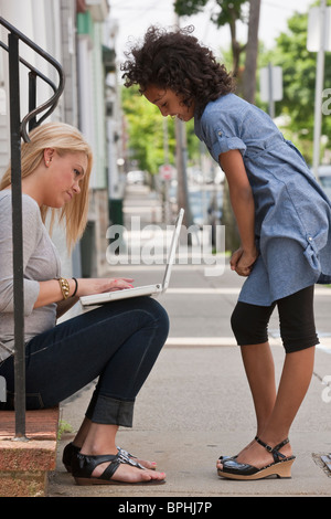 Hispanic teenage girl using a laptop with her sister standing beside her, Boston, Massachusetts, USA - Stock Photo