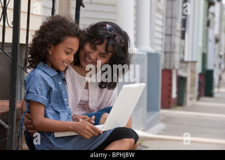 Hispanic girl using a laptop with her mother, Boston, Massachusetts, USA - Stock Photo