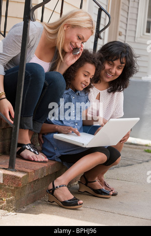 Hispanic girl using a laptop with her mother and sister, Boston, Massachusetts, USA - Stock Photo