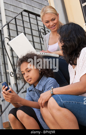 Family using a laptop and mobile phone, Boston, Massachusetts, USA - Stock Photo