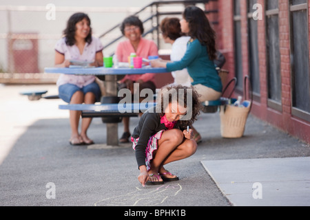 Hispanic girl drawing on the floor with her family in the background, Boston, Massachusetts, USA - Stock Photo
