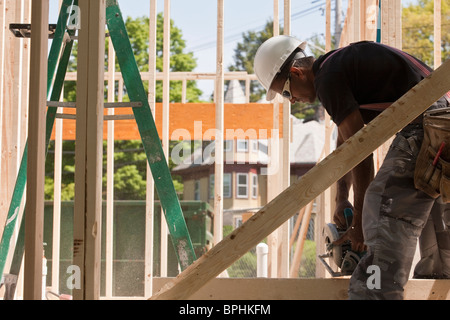 Carpenter using a circular saw at a construction site - Stock Photo