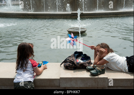 Two girls play on a fountain border in a hot summer day in Milan Italy - Stock Photo