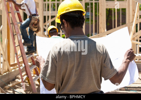 Construction manager reading a blueprint - Stock Photo