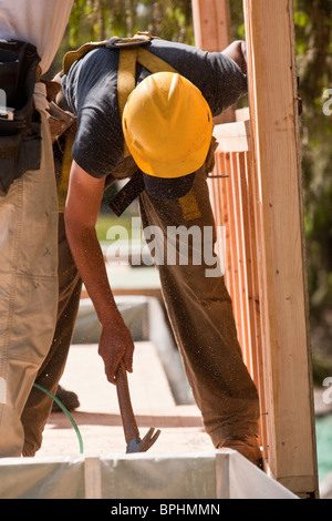 Carpenters using claw hammer at a construction site - Stock Photo