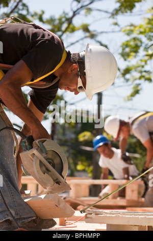 Carpenters using circular saw at a construction site with gable frame in the background - Stock Photo