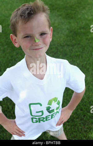 smiling young boy standing  & wearing with 'go green 'tee shirt - Stock Photo