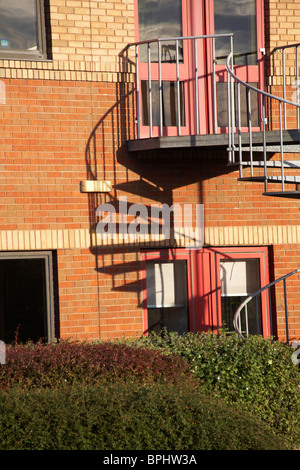 Shadows of fire escape spiral staircase on building in Poole - Stock Photo