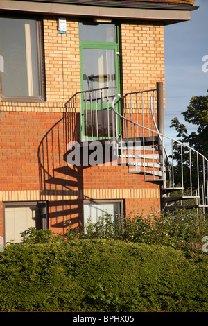 fire escape spiral staircase with shadows on building in Poole - Stock Photo