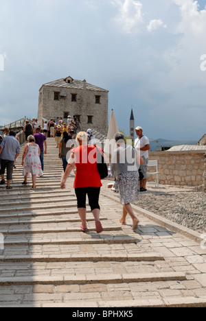 People are walking over the Stari Most, the Old Bridge, that crosses the river Neretva and connects two parts of - Stock Photo