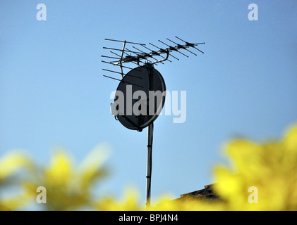 Satellite dish and television aerial on roof of house, Stanwell Moor, Surrey, England, United Kingdom - Stock Photo