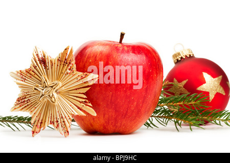 red apple, a straw star and a red Christmas bauble in background with a branch on white background - Stock Photo