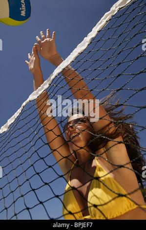 Young woman playing volleyball, wearing a yellow bikini, Mallorca, Balearic Islands, Spain - Stock Photo