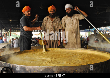 Golden Temple, three Sikh men with giant pot, free food for pilgrims, Sikh holy place, Amritsar, Punjab, India, - Stock Photo