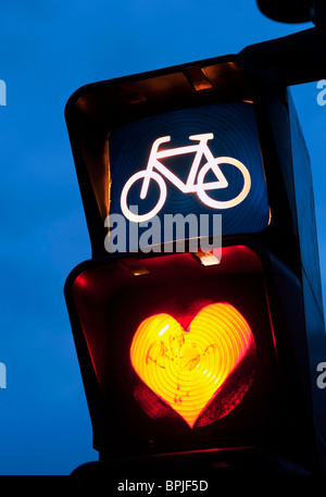 Detail of red cycle traffic stop light painted with love heart in Berlin Germany - Stock Photo