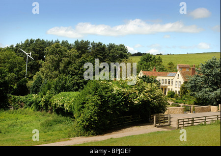 A wind turbine in the garden of a family home with solar panels on the roof in Buckinghamshire UK - Stock Photo