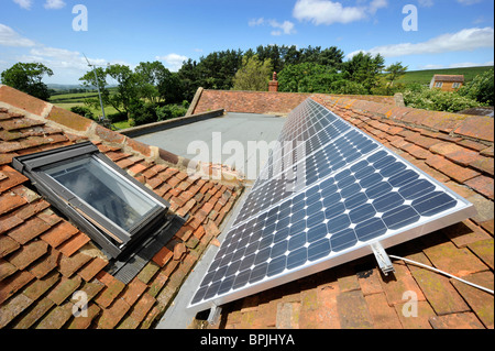Photo-voltaic solar panels on the roof of an eco-friendly home with a wind turbine in the garden in Buckinghamshire - Stock Photo