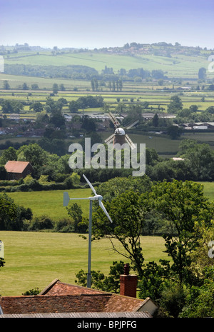 A wind turbine in the garden of a family home with the traditional windmill at Quainton in the distance in Buckinghamshire - Stock Photo