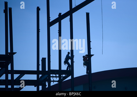 Construction Workers working with iron beams, building a skyscraper. - Stock Photo