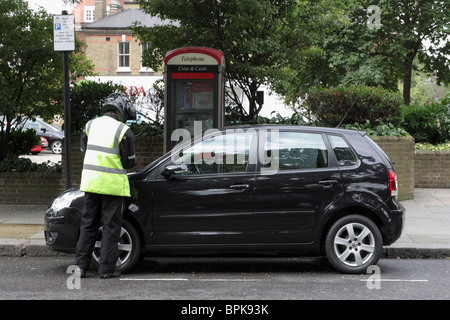 London Traffic Warden issuing a PCN upon a vehicle in Sydney Street, Chelsea, London. - Stock Photo