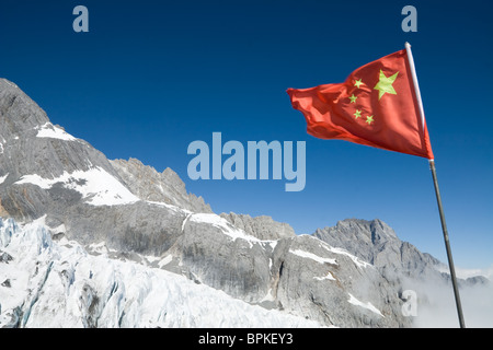 China National flag waving at Yulong (Jade Dragon) Snow Mountain in Lijiang, Yunnan Province, China. - Stock Photo