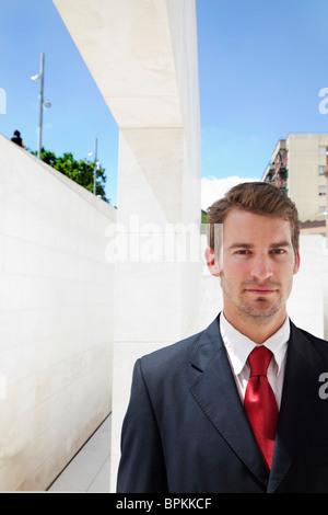 Businessman standing against urban background - Stock Photo