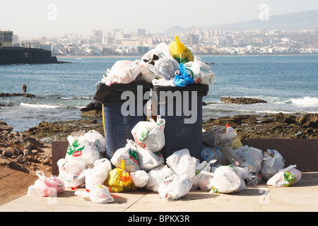 Overflowing wheelie bins on beach in Spain - Stock Photo