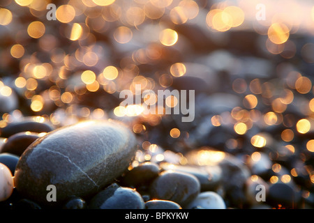 Background with sea stones and orange blurred circles. - Stock Photo