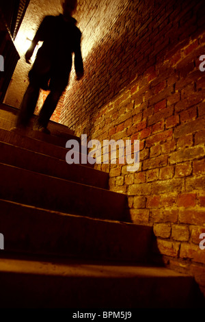 Silhouetted man walking down stairs - Stock Photo