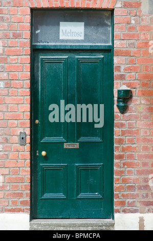 Victorian paneled green front door of brick built terraced house in Llandrindod Wells Powys Mid Wales UK - Stock Photo