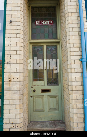 Victorian paneled and glazed scruffy green painted front door of brick built house in Llandrindod Wells Powys Mid - Stock Photo