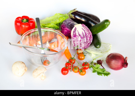 Fresh vegetables and an empty salad bowl. Whole uncut salad ingredients on white background - Stock Photo