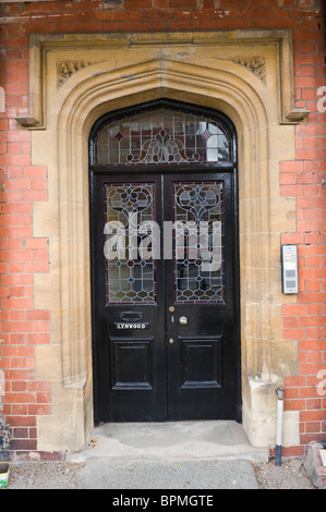 Victorian paneled and glazed black painted gothic style front door of brick built house in Llandrindod Wells Powys - Stock Photo