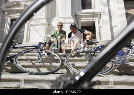 Young couple with bicycles resting on the steps in front of a house, Urbino, Marche, Italy, Europe - Stock Photo