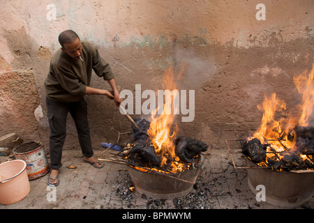 A man stoking the bbq's on the day of Eid al-Adha, Marrakech, Morocco  North Africa - Stock Photo