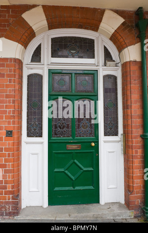 Victorian paneled green painted front door with stained glass of brick built house in Llandrindod Wells Powys Mid - Stock Photo