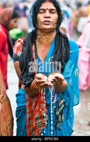 Hindu women praying and bathing in the holy Ganges water. - Stock Photo