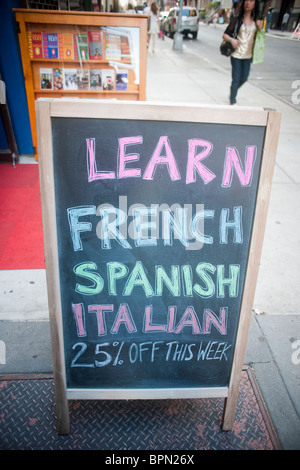 A sign advertising classes in foreign languages in front of a book store in New York - Stock Photo