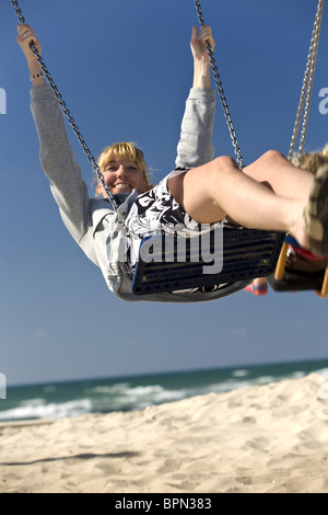 Woman on a swing on Mezizim Beach in Tel Aviv, Israel, Middle East - Stock Photo