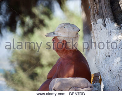 Europe, Greece, View Of Old Greek Man Sitting And Thinking Bare Chest Suntanned - Stock Photo