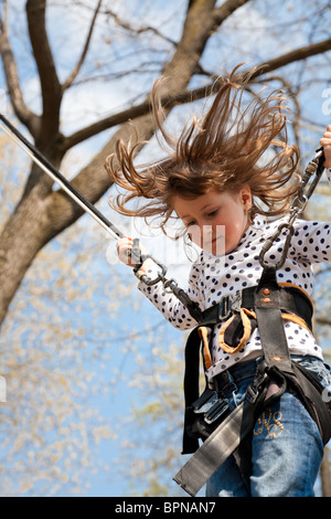 Little girl bouncing with a bungee cord in the park in spring. - Stock Photo