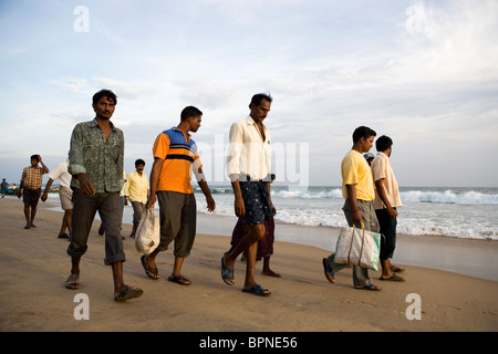 Group of Indian men are walking on the beach after buying fresh fish at the fishing village in Puri, Orissa, India. - Stock Photo