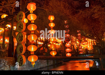 Hanging red lanterns outside restaurants in the old town at dusk.UNESCO World Heritage site. China, Yunnan, Lijiang. - Stock Photo