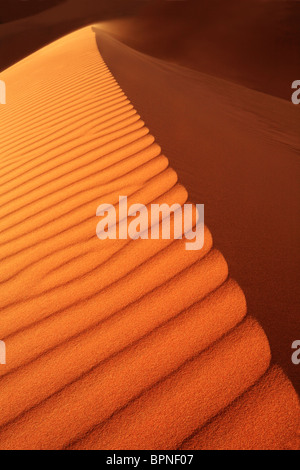 Sand blows from the crest of a dune in Erg Chebbi near Merzouga in Morocco - Stock Photo