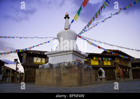 Prayer flags fly from a tibetan chorten/pagoda in a small square in shangri-la (Zhongdian) Yunnan, China. - Stock Photo