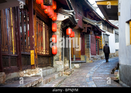 A chinese man walks up a cobbled street in the historic town of Lijiang,UNESCO World Heritage Site,Yunnan Province,China - Stock Photo