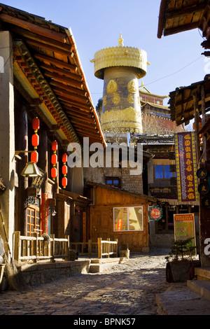 Street behind a Giant khor (Buddhist prayer wheel), in Zhongdian (Shangri-la), China. - Stock Photo