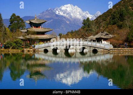 Pagoda and bridge reflected on Black Dragon Pool in front of Jade Dragon Snow Mountain, Lijang, Yunnan, China - Stock Photo
